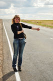 Woman hitchhiking, Road Trip. The blonde is on track and keeps his finger extended upward, backpack behind, vertical Stock Photo