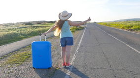 Woman hitchhiking by the roadside. Girl hitchhiking by the roadside stock video footage