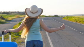 Woman hitchhiking by the roadside stock video