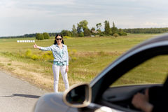 Woman hitchhiking and stopping car at countryside. Road trip, hitchhike, travel, gesture and people concept - woman hitchhiking and stopping car with thumbs up Royalty Free Stock Image