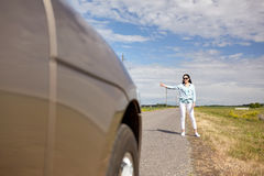 Woman hitchhiking and stopping car with thumbs up. Road trip, travel, gesture and people concept - woman hitchhiking and stopping car with thumbs up gesture at Royalty Free Stock Photos
