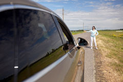 Woman hitchhiking and stopping car with thumbs up Royalty Free Stock Photography