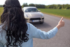 Woman hitchhiking and stopping car with thumbs up Stock Photography