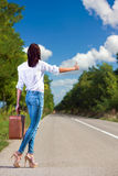 Woman hitchhiking with a suitcase. Back view Royalty Free Stock Image