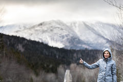 Woman Hitchhiking on a Winter Road with Beautiful Snowy Mountain. Lonely Young Woman Hitchhiking on a Winter Road with Beautiful Snowy Mountains in Background Stock Photography