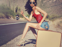 Woman hitching a ride on desert road Royalty Free Stock Images