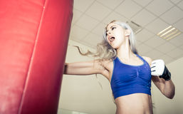 Woman hits the boxing heavy bag in the gym Royalty Free Stock Image