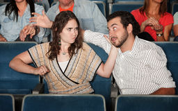 Woman Hits Man in Theater. Irked women gestures to punch men in theater Stock Image