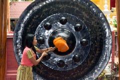 Woman hitting a gong stock photo
