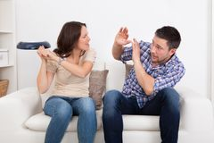 Woman hitting man with sauce pan Stock Photos