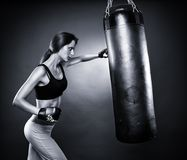 Woman hitting the punching bag Royalty Free Stock Photography