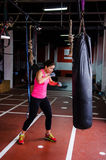 Woman hitting the punching bag Stock Photos