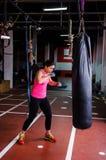 Woman hitting the punching bag stock photos