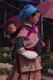 Woman Hmong flowered market of Lai Chau. Like all mothers, she is not separated from her baby she is carrying in the back Stock Photo