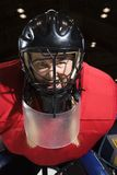 Woman hockey goalie. Woman hockey goalie wearing helmet sneering looking intimidating Stock Photography