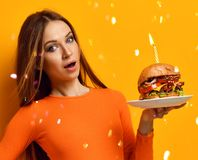 Woman hands hold big burger barbeque sandwich with beef and lit candle for birthday party on yellow Royalty Free Stock Images