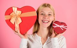 Woman hold big and little heart shaped gift boxes. Which one she prefer. Girl decide which gift she like more. Big. Surprise and small gift. Make choice stock photo