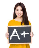 Woman hold blackboard showing sign of A plus Royalty Free Stock Photography