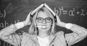Woman hold book bite pen chalkboard background. Learn be inspiring teacher. Inspiring teacher spark motivation. Looking. For inspiration. Inspired work harder royalty free stock images