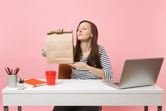 Woman hold brown clear empty blank craft paper bag, sniffing smell work at office with pc laptop isolated on pink. Background. Food products delivery courier royalty free stock images