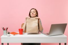 Woman hold brown clear empty blank craft paper bag, sniffing smell work at office with pc laptop isolated on pink. Background. Food products delivery courier royalty free stock photo