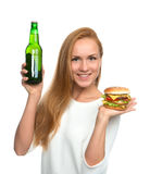 Woman hold burger sandwich in hand and bottle of beer Stock Photos