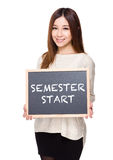 Woman hold with chalkboard showing phrases of semester start Stock Photos