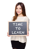 Woman hold with chalkboard showing the phrases of time to learn. Isolated on white background Royalty Free Stock Photography