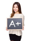 Woman hold with chalkboard showing sign of A plus. Isolated on white background Stock Images