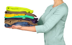 Woman hold clothes pile against Royalty Free Stock Photo