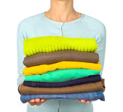 Woman hold clothes pile against Stock Images
