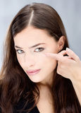 Woman hold conctact lens in front of eye Stock Images