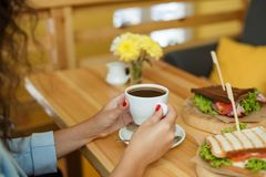 Woman hold a cup of coffee at backgroud wooden table, on which lies a sandwich.  royalty free stock photos