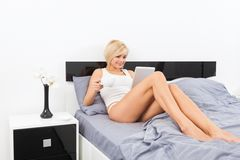 Woman hold cup coffee on bed using digital tablet Royalty Free Stock Photos