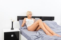 Woman hold cup coffee on bed using digital tablet Stock Photos