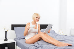Woman hold cup coffee on bed using digital tablet Royalty Free Stock Photography