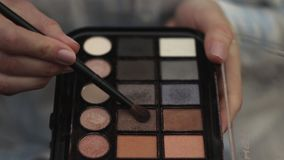 Woman hold eye shadow palette and with second hand take shadow with brush . Woman hold eye shadow palette and with second hand take shadow with brush stock video