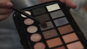 Woman hold eye shadow palette and with second hand take shadow with brush.  stock video