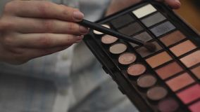 Woman hold eye shadow palette and with second hand take shadow with brush.  stock footage