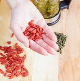Woman hold goji closeup. Teapot, green tea, goji on the table closed up Stock Image