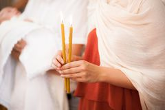 Woman hold in hands two candels in church atmosphere Stock Photo