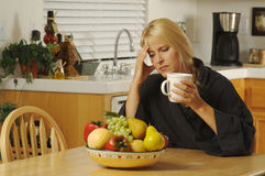 Woman hold head and coffee. Royalty Free Stock Photo