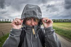 Woman hold her hood of the jacket with both hands Stock Photography