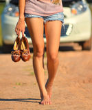 A woman hold her shoes and walk Stock Photo