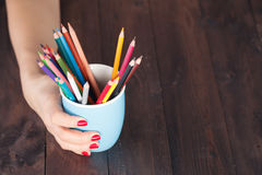 Woman hold mug with many color pencil stock photography