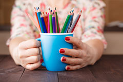 Woman hold mug with many color pencil Royalty Free Stock Images