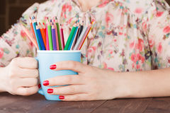 Woman hold mug with many color pencil Royalty Free Stock Photography