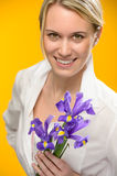 Woman hold one spring iris flower smiling Royalty Free Stock Photography