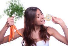 Woman hold organic fresh carrots tablet pills Stock Image