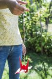 Woman hold origami crane. Woman hold red origami crane in the garden stock photography